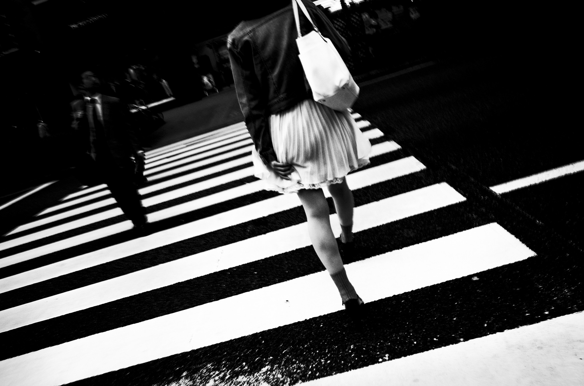 Girl crossing the street in Tokyo, holding her skirt lifted by the wind.